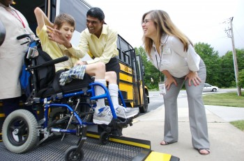 Parent watches as student in wheelchair is unloaded from bus