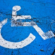 Handicapped sign depicted white wheelchair on blue graphic