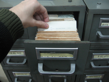 Hands searching through library card catalog