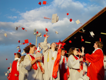 Graduates throw hats up in the air