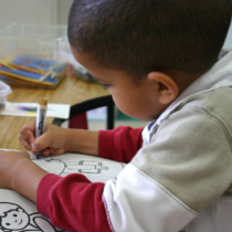 Young boy coloring at a desk