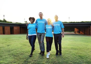 Four people wearing identical T shirts walk in a sunny field